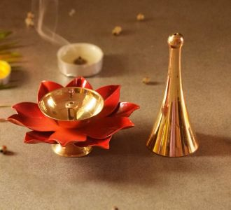 In Shades Of Orange And Golden Composed Of Brass And Aluminium Graceful Diya And Bell Set